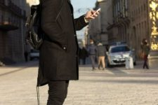 Black parka with leather backpack, skinny pants and lace up boots