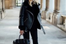 Black shearling jacket with skinny pants, high boots and leather bag