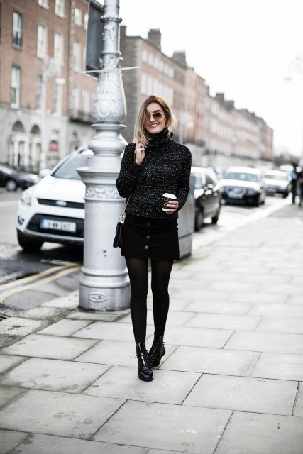 Black turtleneck, mini skirt, flat boots and small bag