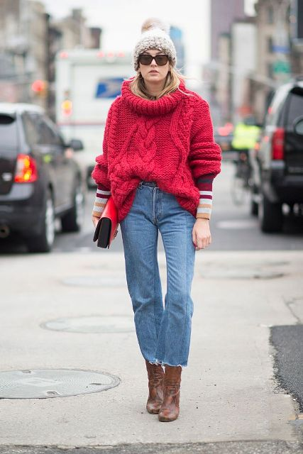 With beige beanie, red oversized sweater, brown mid calf boots and red clutch