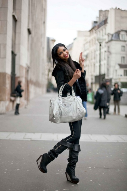 With black jacket, black pants and metallic bag