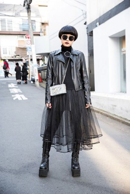 With black leather jacket, black turtleneck, mini bag and sheer skirt