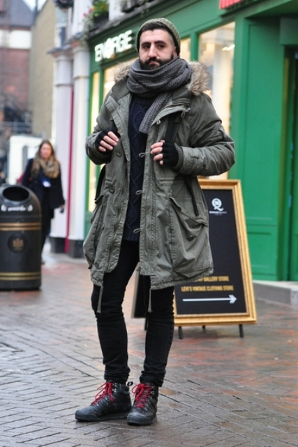 With black shirt, black pants, boots, gray scarf, olive green beanie and backpack