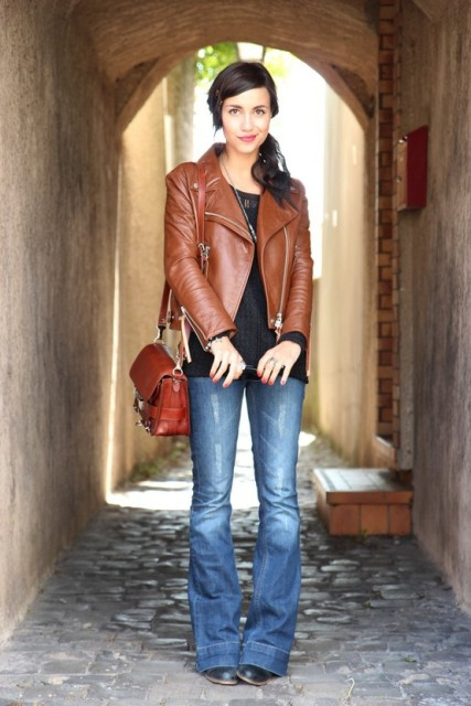 With black shirt, brown leather jacket, red bag and black boots