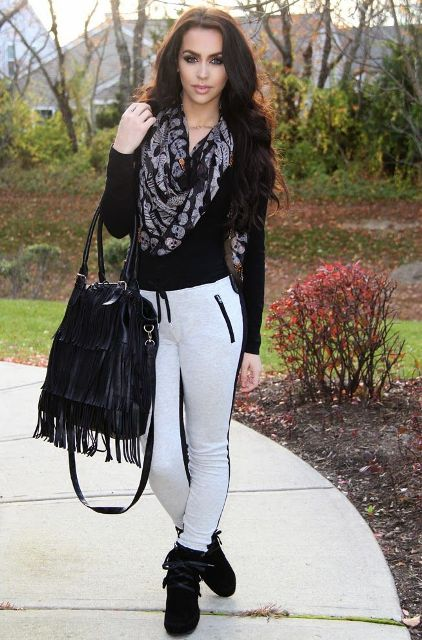 With black shirt, fringe bag, black boots and printed scarf