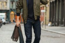 With black shirt, olive green jacket, gray beanie and brown shoes