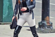 With black shirt, white skinny jeans, hat and leather jacket
