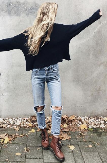 With black sweater and brown flat boots