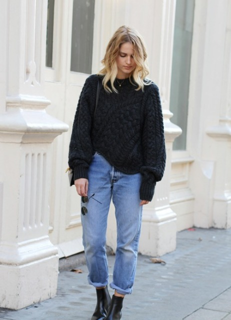 With black sweater, ankle boots and small bag
