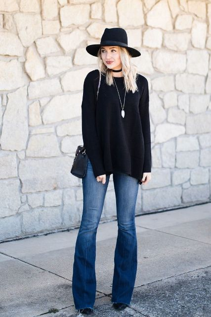 With black sweater, black wide brim hat and mini bag