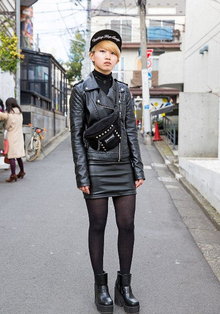 With black turtleneck, leather skirt, leather jacket, cap and suede bag