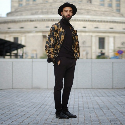 With black turtleneck, pants, boots and printed jacket