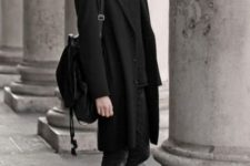 With black turtleneck, skinny pants, black coat, metallic shoes and backpack