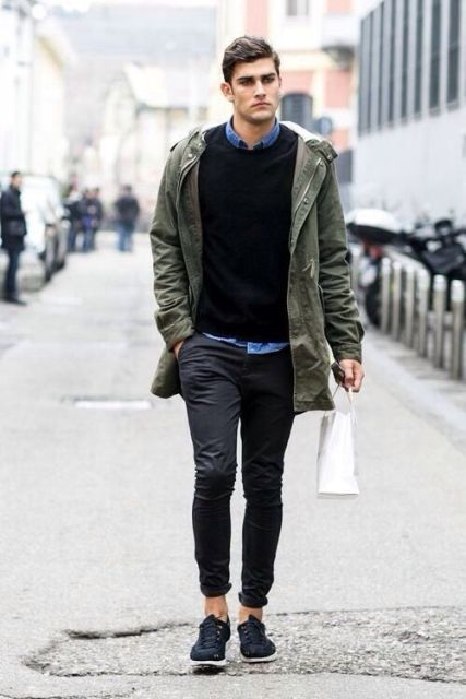 Black cuffed pants with denim shirt, black sweater, olive green parka and sneakers