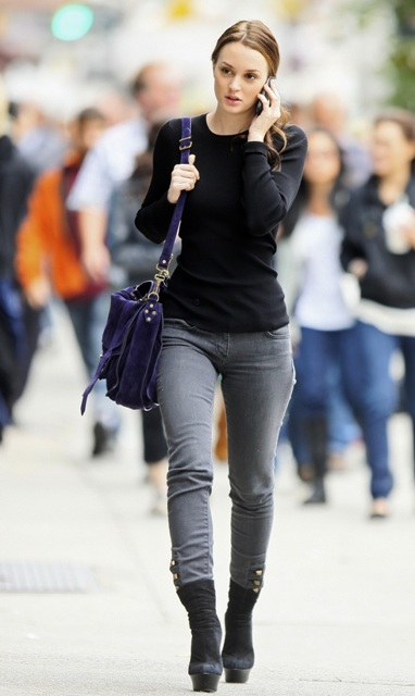 With gray jeans, black shirt and purple bag
