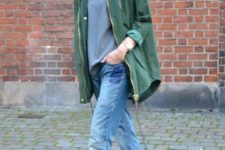 With gray sweatshirt, black boots and green parka
