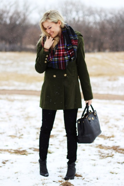 With green coat, black pants, ankle boots and black bag