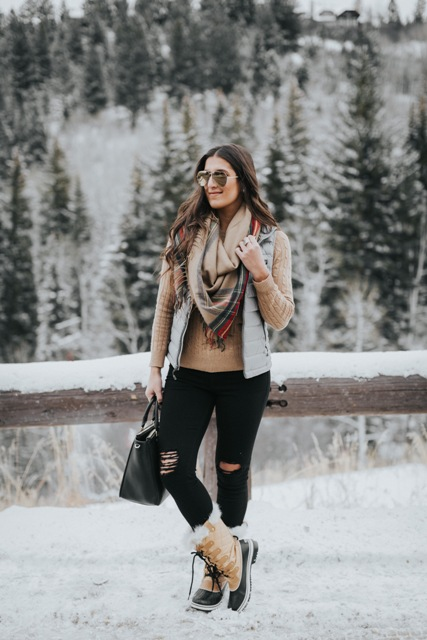With light brown shirt, gray vest, distressed pants, duck boots and black bag