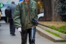 With olive green bomber jacket, heels and chain strap bag