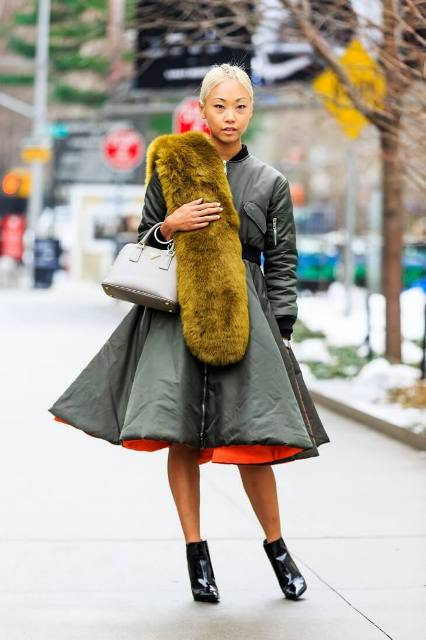 With olive green coat, fur neckpiece and white bag