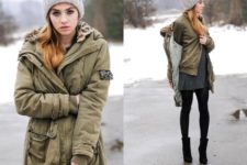 With olive green jacket, gray dress, mid calf boots and gray beanie