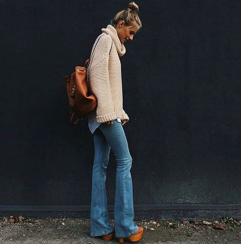 With oversized sweater, brown platform shoes and backpack