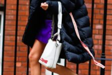 With purple mini skirt, navy blue puffer coat and white bag