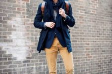 With striped shirt, navy blue coat, brown leather backpack and mid calf boots