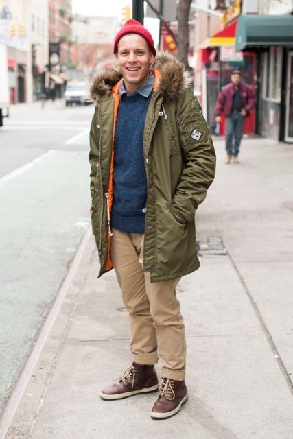 With sweater, green parka, red beanie and brown boots