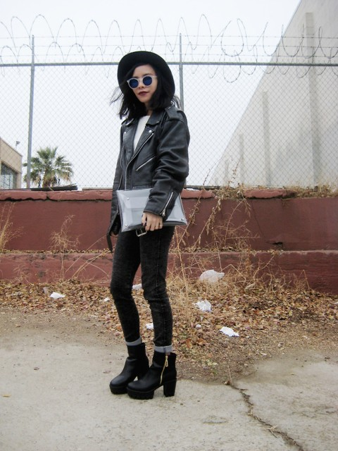 With white shirt, black leather jacket, wide brim hat, cuffed pants and clutch