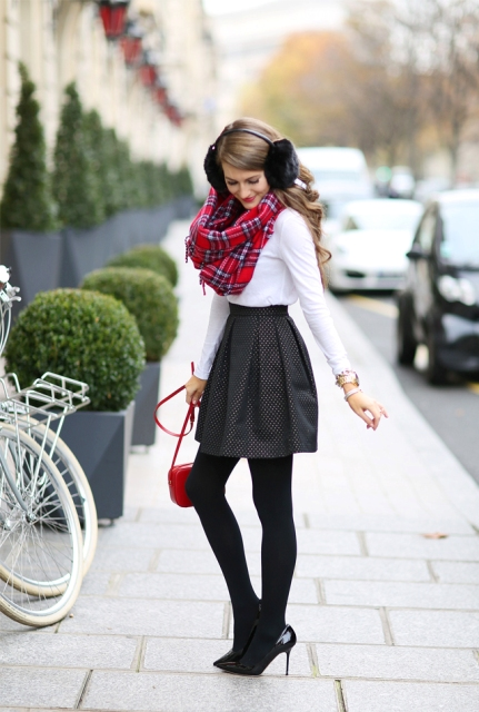 With white shirt, printed skirt, black tights, black heels and red bag