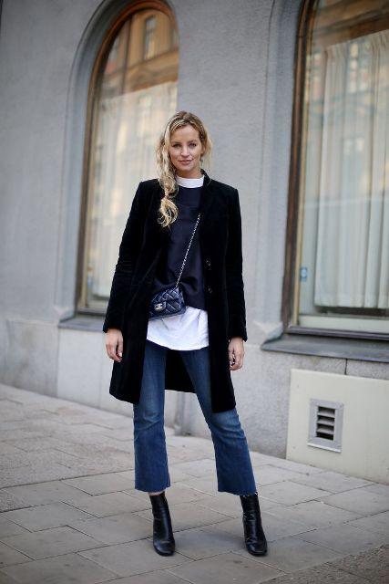 With white shirt, sweater, black coat, mini bag and mid calf boots