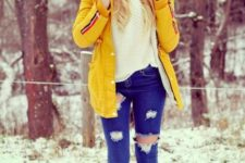 With white sweater, beanie, brown boots and distressed jeans