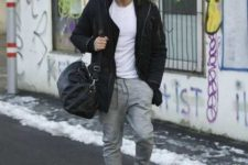 With white t-shirt, gray joggers, beige sneakers and black bag