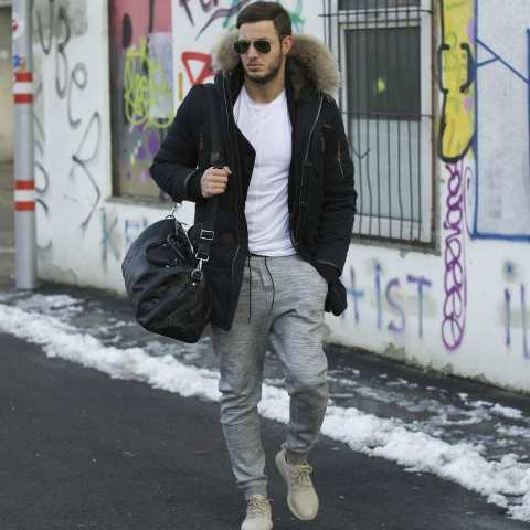 With white t shirt, gray joggers, beige sneakers and black bag