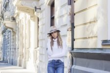 With white turtleneck, black boots and beige hat