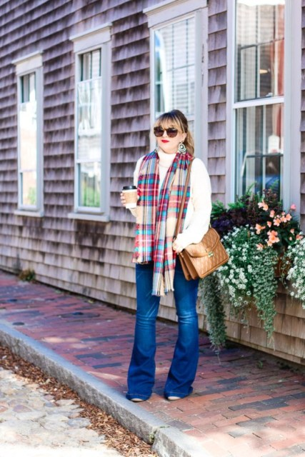With white turtleneck sweater, brown bag and plaid scarf