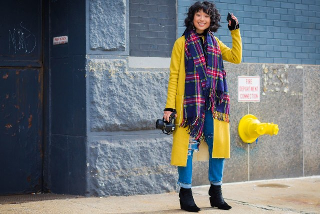 With yellow coat, cuffed jeans and black ankle boots