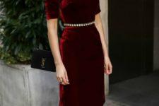 02 a burgundy velvet over the knee dress with short sleeves, a high neckline and an embellished belt