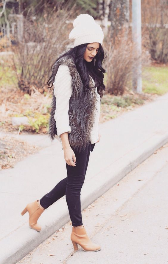 black jeans, amber boots, a white shirt, a brown faux fur vest and a beanie