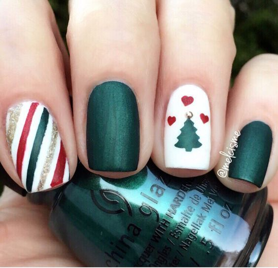 dark green, white, red and gold nails with a striped one and a tree one