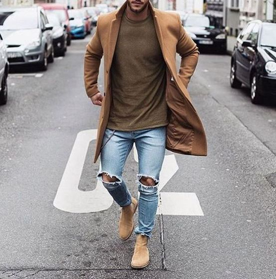 a brown tee, a camel coat, beige boots and ripped blue jeans