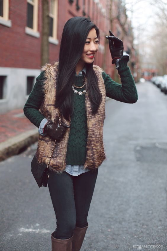 black skinnies, a shirt, a green sweater, a faux fur vest and knee boots