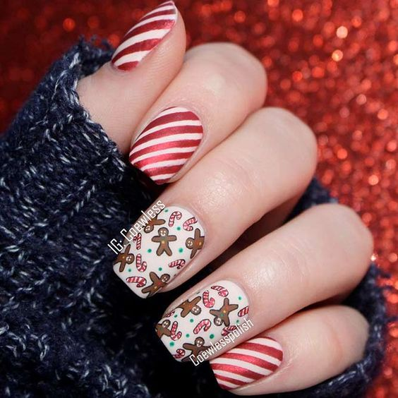 red and white striped nails with two accent nails with candy canes and gingerbread men