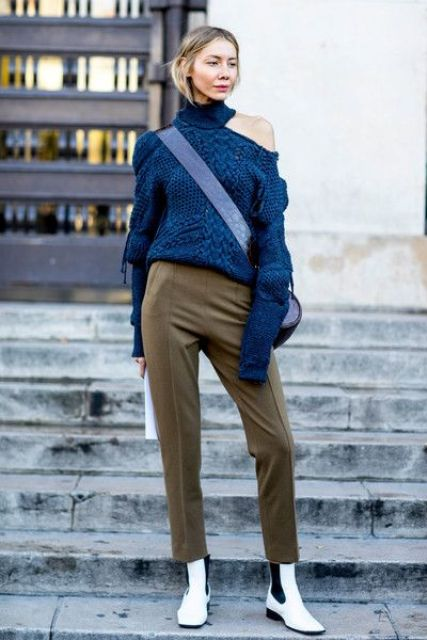 tan pants, white chelsea boots, a blue cable knit one shoulder sweater