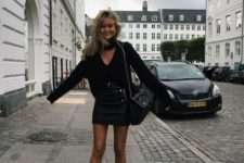 04 a black leather mini skirt, a black sweater with a cutout and grey sock booties