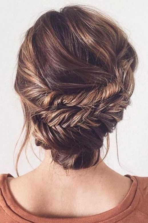 a wavy low fishtail braid updo with some bangs