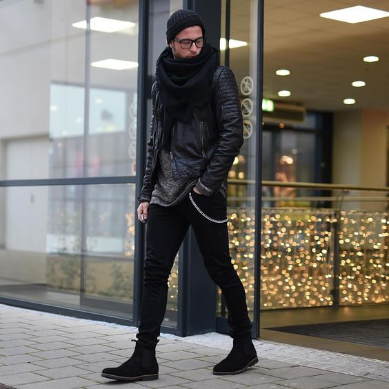 black jeans, black chelsea boots, a grey sweater, a black leather coat, scarf and beanie