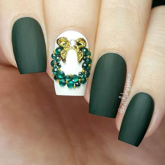 gorgeous Christmas manicure in matte dark green with a white accent nail and an emerald rhinestone wreath