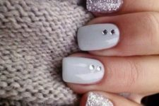 04 silver glitter manicure with two white ones and rhinestones on them